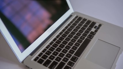 Computer pan across keyboard reflecting windows