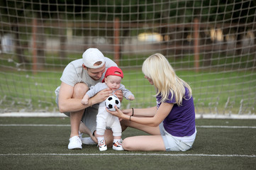 the father, mother and the kid play soccer
