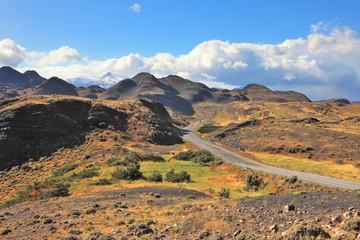 The gravel road curls among hills