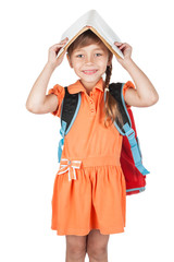 Cute schoolgirl with book on his head and a red backpack on her