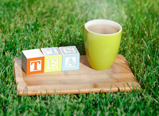 Cup of tea and wooden blocks at grass