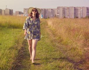 Happy girl walking on summer field.