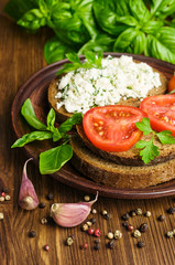 sandwiches of rye bread with cheese, tomato and basil