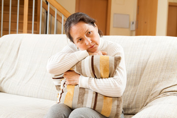moody senior woman sitting on sofa