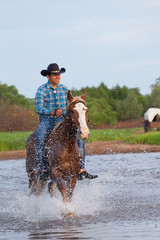 cowboy on a horse skips down the river