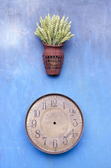 ancient clock face and wicker basket with wheat ears on wall