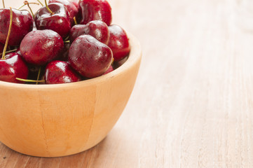Fresh cherries in bowl on table