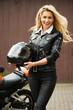 Lachende junge Frau mit Motorradhelm