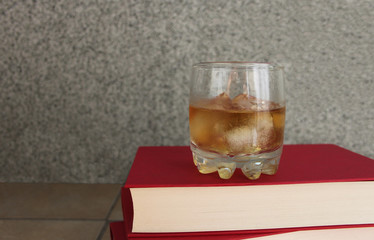 Glass of whiskey with ice on pile of red books