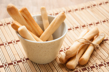 Breadsticks on wooden background.
