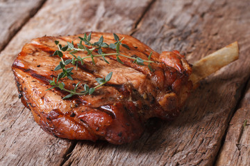 hot juicy pork steak with thyme on an old table