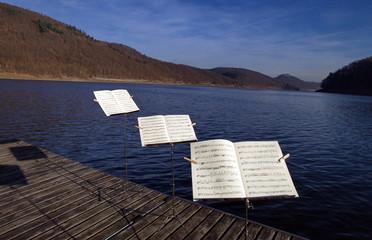 Drei Notenständer hintereinanderstehend auf einem Steg am See