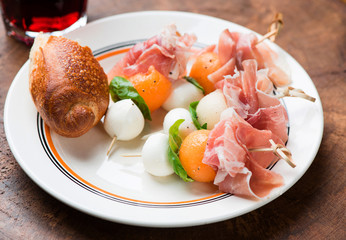 Appetizer with melon,mozzarella and prosciutto on skewers