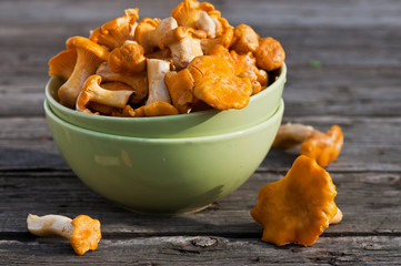 Chanterelles on the old board in the green plate