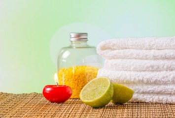 Spa massage with towel stacked,red candle and lime