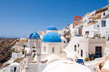 Oia church with blue domes and bell on the Santorini, Greece