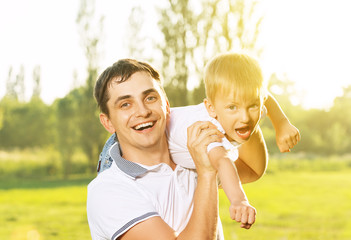 happy Dad and son hugging, playing and laughing in summer nature