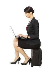 Business woman looking at notebook sitting on suitcase, isolated