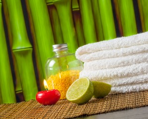 Spa massage towel stacked red candle and lime