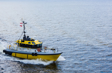 Yellow and Black Pilot Boat in Corner of Frame