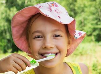 Summer portrait of adorable  little girl brushing teeth