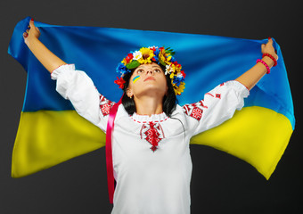 Attractive girl in national dress with a Ukrainian flag