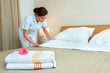 Maid making bed in hotel room - 68906562