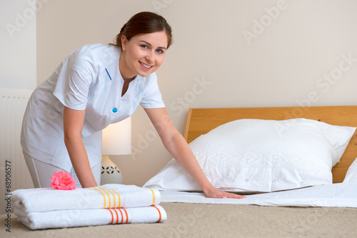 Maid making bed in hotel room - 68906577