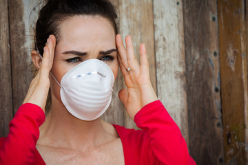 Woman wearing a face mask has a headache