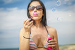 Woman blowing bubbles at the sea