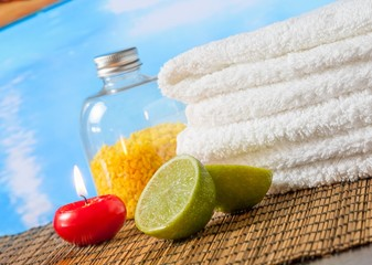 Spa massage with towel red candle and lime near swimming pool
