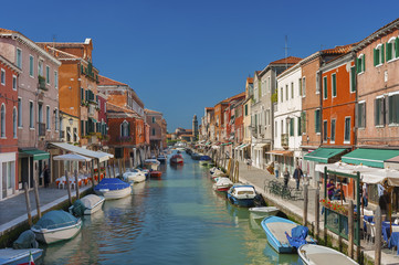 Murano island canal, colorful houses and boats, Italy.