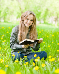 girl sitting on grass with dandelions reading a book and looking