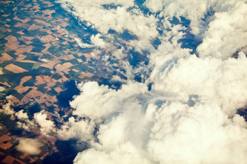 Aerial view of cloudscape and earth with fields