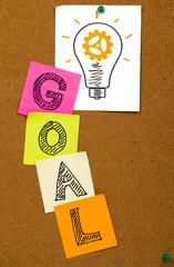 goal concept with idea bulb on cork noticeboard