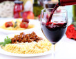 Pouring red wine and food background