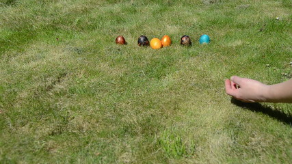 Traditional Easter game. Hand throw roll colorful eggs on grass.