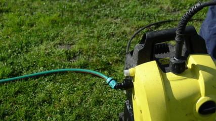man hand detach water hose to high pressure wash equipment