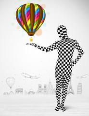 man in full body suit holding balloon
