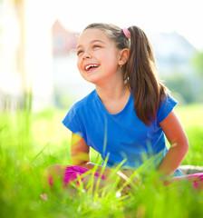 Portrait of a little girl sitting on green grass