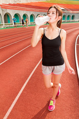 Chinese woman drinking water after jogging