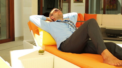 Young businessman sleeping on lounger bed by the villa