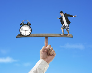 businessman standing on finger seesaw vs clock