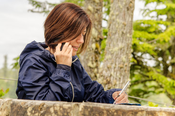 Woman Taking Notes while on Phone in a Park