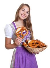 Frau im lila Dirndl mit Brezeln frisch aus dem Ofen