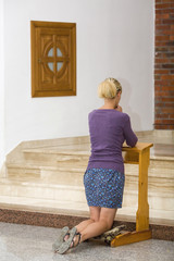 Handsome young woman praying in a church