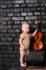 little boy with violin on brick wall background for text music