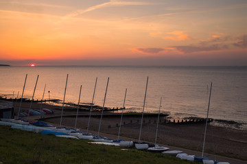 Sunset in Whitstable, Kent, UK with masts from moored yachts.