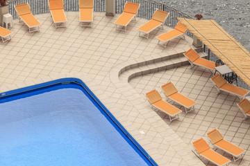 Schwimmbecken mit Liegestühlen am Meer