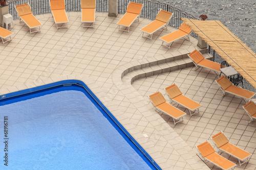 canvas print picture Schwimmbecken mit Liegestühlen am Meer